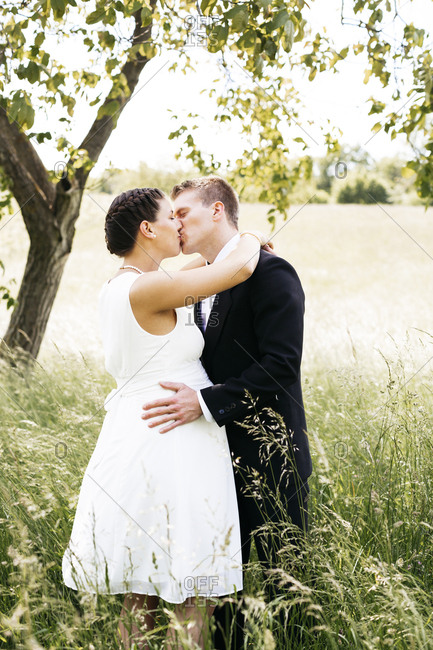 Pregnant bride kissing her husband on a meadow