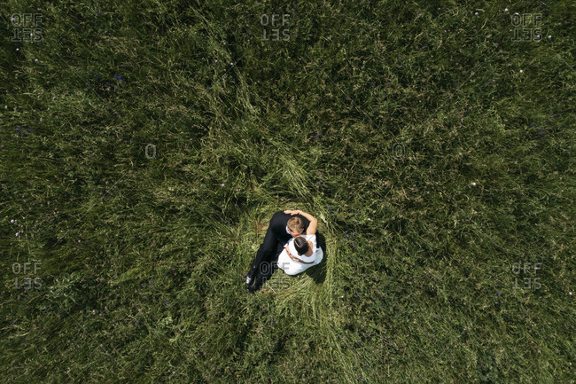 Aerial view of pregnant bride with her husband sitting on a meadow