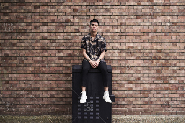 Portrait of young man in front of brick wall