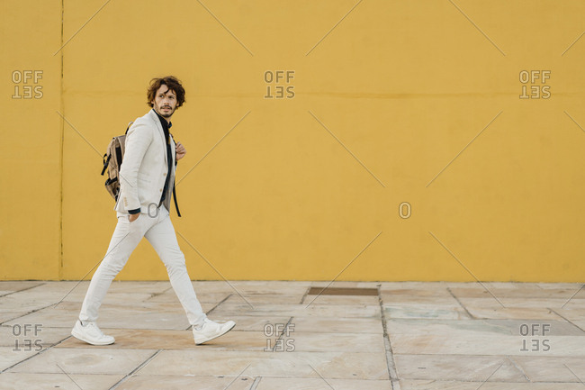 Portrait of walking businessman with backpack in front of yellow wall