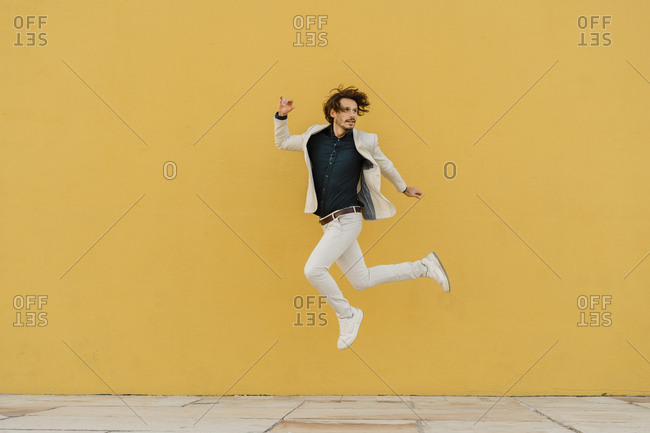Businessman jumping in the air in front of yellow wall