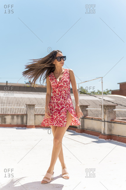 Portrait of young woman on roof top wearing fashionable summer dress tossing her hair