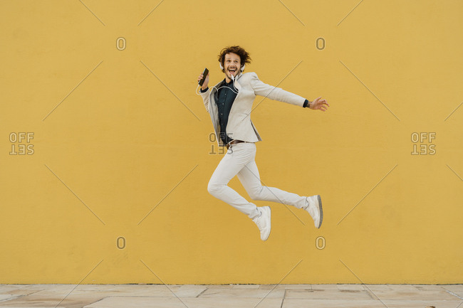 Happy businessman jumping in the air in front of yellow wall listening music with headphones
