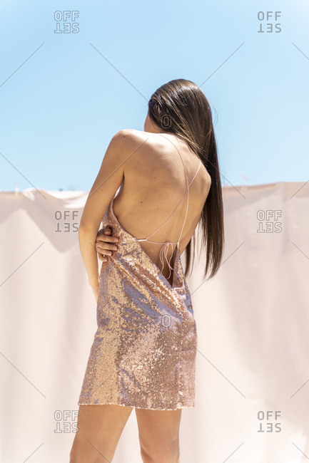 Back view of woman on roof top wearing backless evening dress