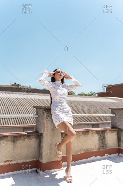 Woman on roof top wearing fashionable white dress