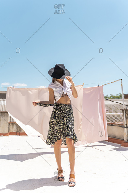 Fashionable young woman wearing hat- wrap-around blouse and skirt with floral design