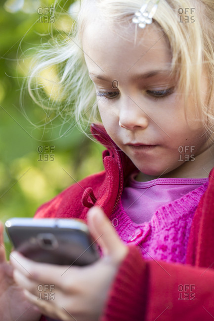 Portrait of little girl using smartphone