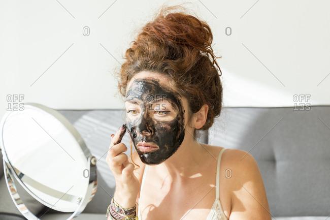 Young woman applying facial mask at home