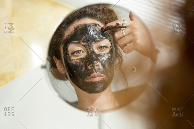 Mirror image of young woman applying facial mask at home