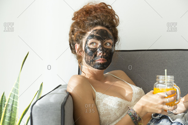 Young woman wearing facial mask and having a drink at home