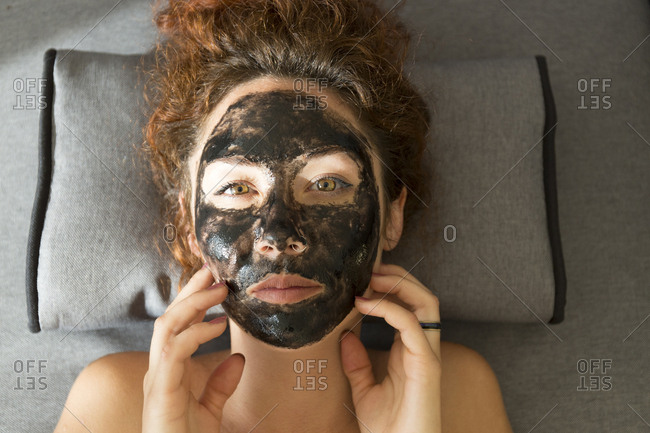 Portrait of young woman lying down wearing facial mask