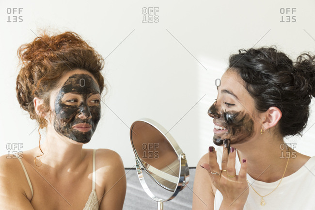 Two happy young women applying facial masks at home