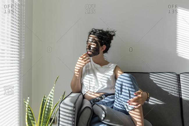 Relaxed young woman wearing facial mask at home