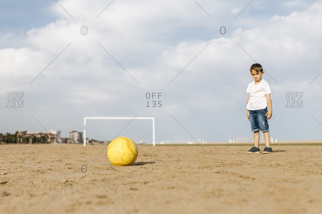 Boy ready to make a shot with a ball on the beach