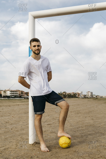 Portrait of a man with football on the beach