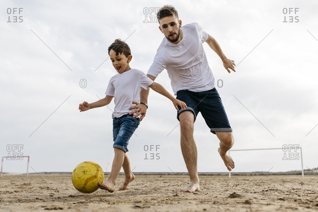 Boy and man playing soccer on the beach