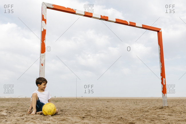 Boy sitting on the beach and leaning against soccer goal