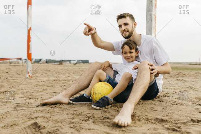 Man and boy resting after soccer game on the beach
