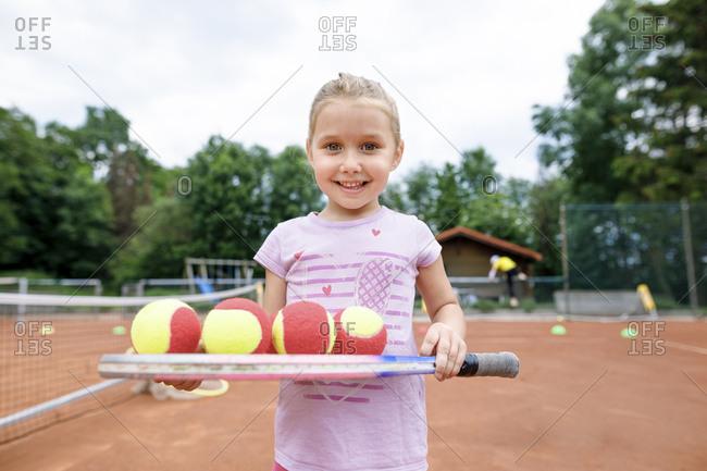Little girl- lerning to play tennis- balancing balls on a racket