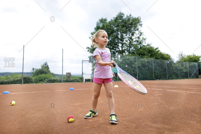 Little girl- lerning to play tennis