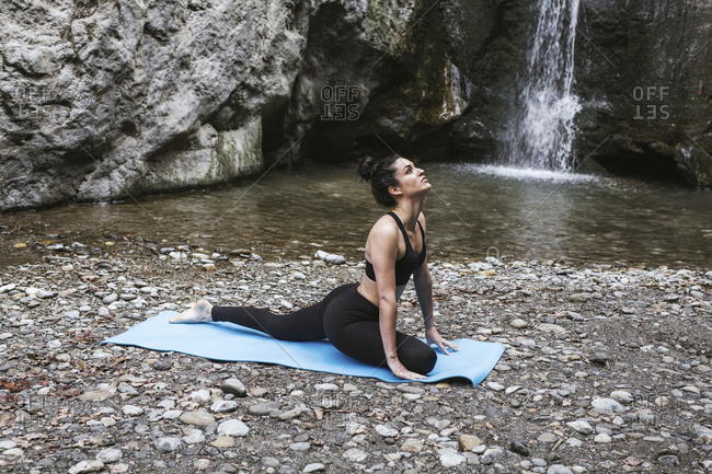 Woman practicing yoga at waterfall-  cobra pose