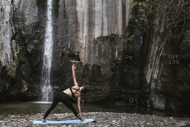 Woman practicing yoga at waterfall- triangle pose