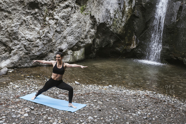 Woman practicing yoga at waterfall- warrior pose