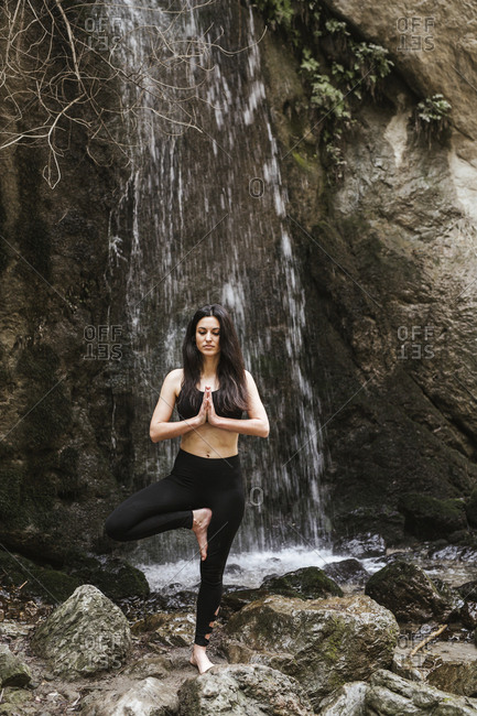 Woman practicing yoga at waterfall- tree position