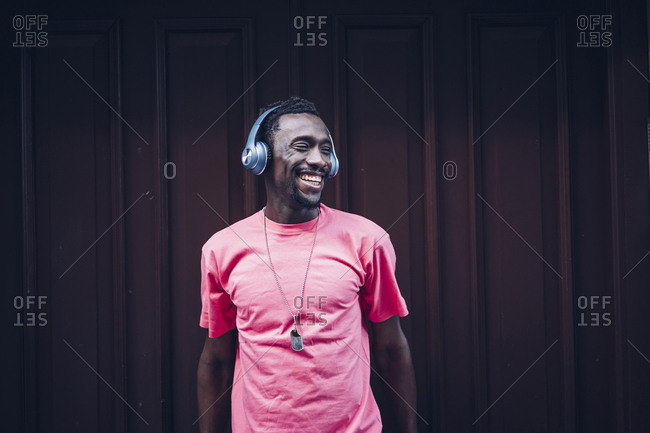 Laughing man wearing pink t-shirt listening to music with headphones