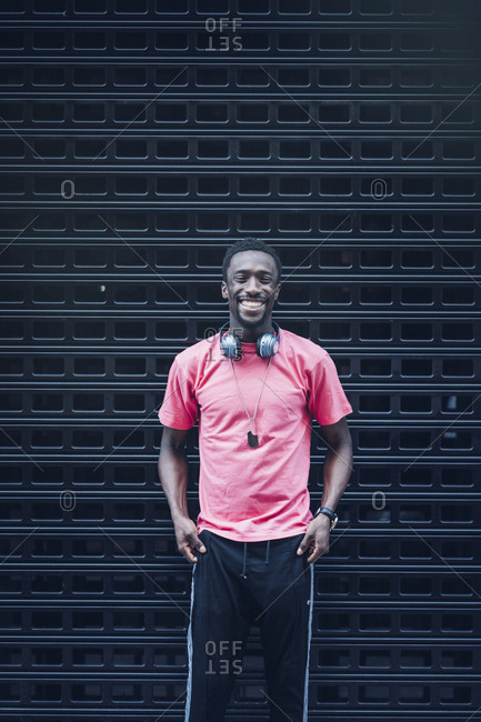 Portrait of laughing man with headphones wearing pink t-shirt