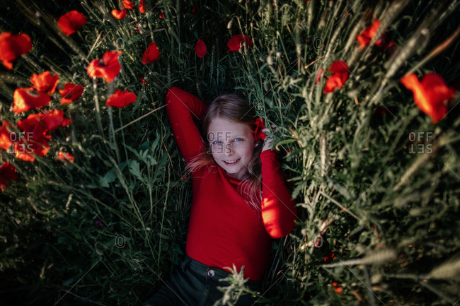 Little girl lying in poppy field