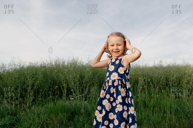 Portrait of happy little girl wearing summer dress with floral design
