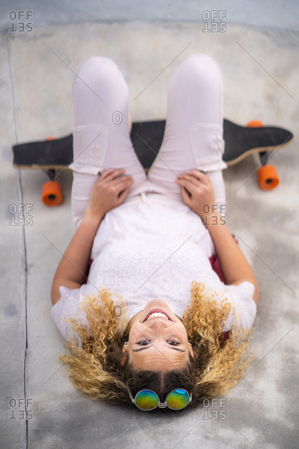 Smiling young woman with a long board at a skate park