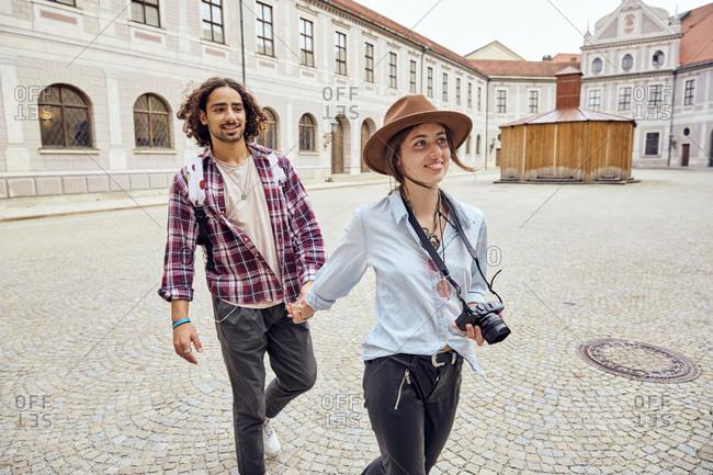 Young tourist couple walking in courtyard of Munich Residenz- Munich- Germany