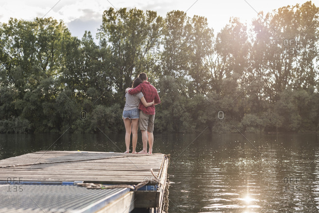 Young couple embracing on jetty at a remote lake