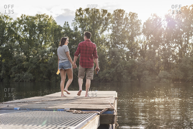 Young couple walking hand in hand on jetty at a remote lake