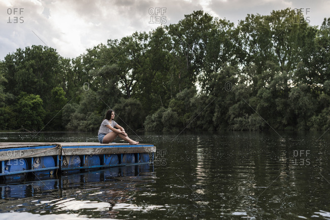 Relaxed woman sitting on jetty at a remote lake
