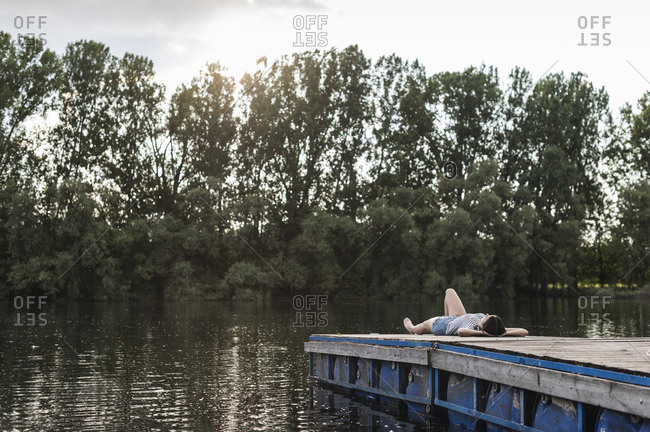 Relaxed woman lying on jetty at a remote lake
