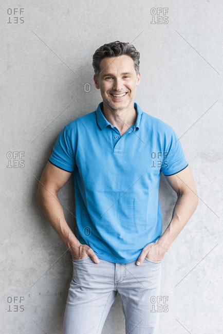 Mature man wearing blue polo shirt- grey wall in the background