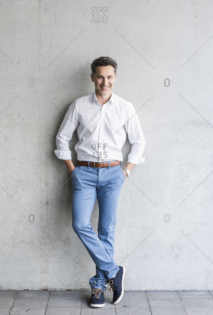 Businessman wearing white shirt- grey wall in the background