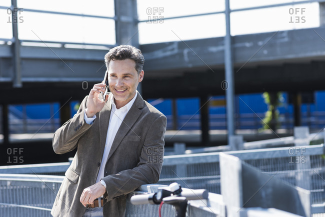 Businessman using smartphone- E-Scooter leaning on railing