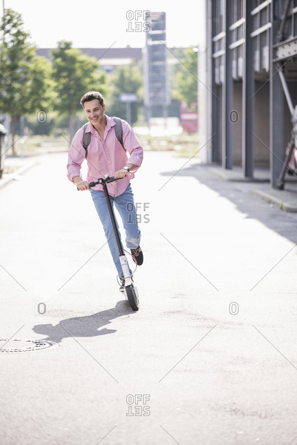 Businessman with backpack riding his E-Scooter