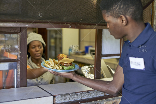 Young waiter taking delivered food from the restaurant kitchen- South Africa