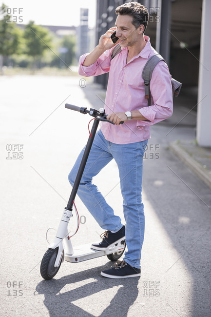 Businessman using smartphone- standing on E-Scooter