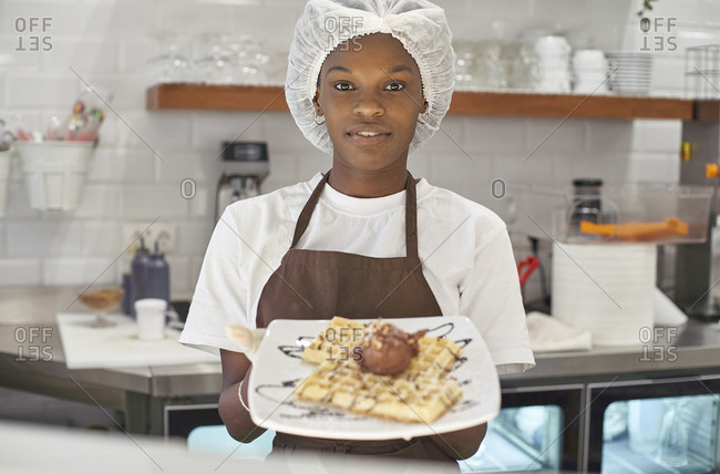 Young woman working in ice cream parlor- serving waffles with ice-cream