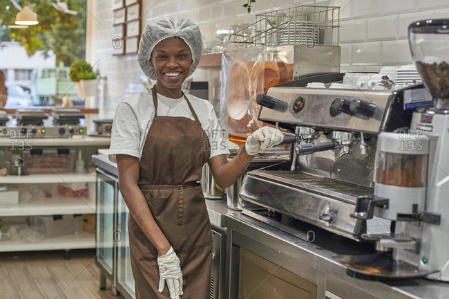 Young woman working in ice cream parlor- operating coffee machine