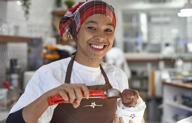 Young woman working in ice cream parlor- filling cup with ice-cream