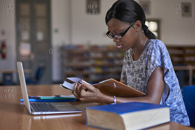 Young student with laptop reading a book at National library- Maputo- Mocambique