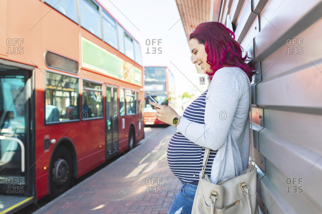 Pregnant woman using her phone at bus stop