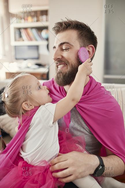 Father and daughter playing superhero and superwoman- girl brushing beard